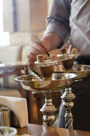 Preparing the shisha, aka nargile or hookah at a restaurant by placing the charcoals on top  A very middle eastern custom