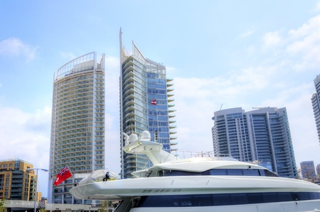 embarked: A view of a yacht and towers at the beautiful Marina in Zaitunay Bay in Beirut, Lebanon  A very modern, high end and newly developed area where yachts are embarked and it