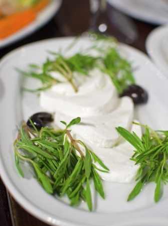 Lebanese food starter, labneh slices topped with thyme and olives  A photo of a very typical dish of Lebanon and Mediterranean cuisine