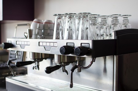 A professional espresso coffee maker, ideal for cafes and bars  Stored over it are late glasses and coffee cups photo