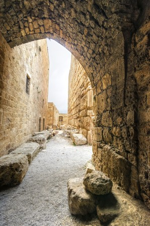 The interior of the crusaders castle in the historic city of Byblos in Lebanon. A view of an arc and the walls of the castle leading to the courtyard, facing the east side. photo