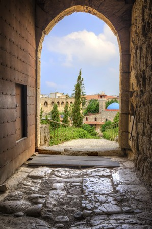 The historic city of  Byblos in Lebanon viewed from the gate entrance of the crusaders castle. A view of the mosque and the path leading to the castle entrance. photo
