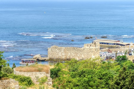 The ancient and historic port of Byblos in Lebanon. A view of the ancient walls surrounding it and a boat entering the port from the Mediterranean sea.