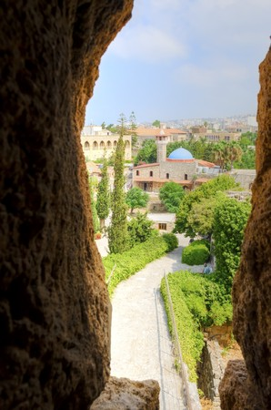 The historic city of  Byblos in Lebanon viewed from the arrow loop of the crusaders castle. A view of the mosque and the path leading to the castle entrance.