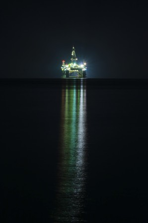 A night view of the oil drilling platform lit up on the coast of Limassol, in Cyprus  The oil rig is floating in the Mediterranean sea and is ready for drilling for natural gas appraisal   Stock Photo