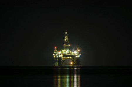 oil park: A night view of the oil drilling platform lit up on the coast of Limassol, in Cyprus  The oil rig is floating in the Mediterranean sea and is ready for drilling for natural gas appraisal   Stock Photo