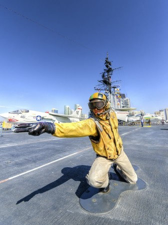A statue of a Flight Deck Director, catapult officer, signalling aircrafts into position on the starboard catapult, in preparation for launching on the historic USS Midway Museum in San Diego, California, United States of America