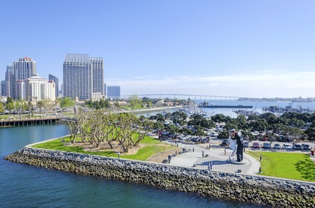 A view of the Unconditional surrender statue in Downtown San Diego marina in southern California in the United States of America  Some of the local architecture, commercial buildings and the coronado bridge in the city  Stock Photo