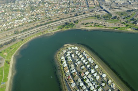 An aerial view of San Diego Mission Bay in southen California, United States of America. A view of the coastline, De Anza cove and peninsula, Mission Bay park, San Diego Fwy and the local houses. photo