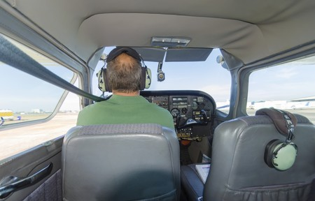 A rear view of a cessna pilot ready for take off. A small airplane with leather seats, with a passenger compartment and small control panel in the cockpit.