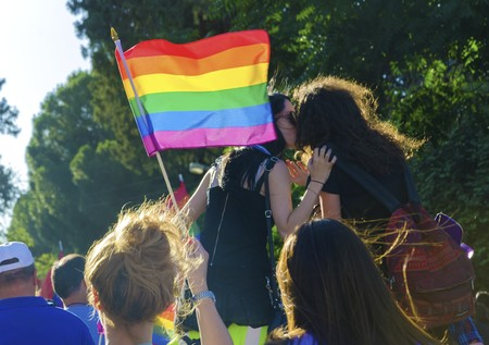 bisexual: NICOSIA, CYPRUS - 31 MAY 2014: The first Gay Pride Parade in Cyprus to celebrate LGBT, lesbian, gay, bisexual and transgender rights. A Rainbow flag waving around and two girls kissing and marching for human rights.