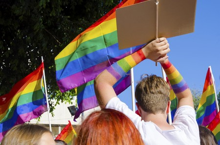 The first Gay Pride Parade in Cyprus to celebrate LGBT, lesbian, gay, bisexual and transgender rights. A man with rainbow colored hands raised and rainbow flags waving around in Plateia Eleuthereias in Nicosia.