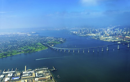 Aerial view of the Coronado island and bridge in the San Diego Bay in Southern California, United States of America. A view of the Skyline of the city and some boats crossing the the sea. Stock Photo