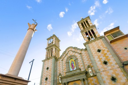 The Catedral de Nuestra Senora de Guadalupe, the first catholic church in Tijuana, Mexico of the Lady of Guadalupe. A view of the exterior of the cathedral, the arch, two towers, columns, clock and cross. Banco de Imagens