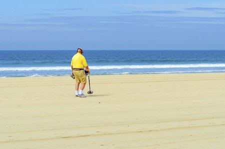 An old man walking along the coast holding a portable metal  detector on the Pacific beach in America, pointing the long stick at the sand, trying to find metallic objects scanning the area and wearing headphones. photo