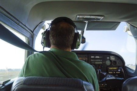 cessna: A rear view of a cessna pilot ready for landing. A small airplane with leather seats, with a passenger compartment and small control panel in the cockpit.