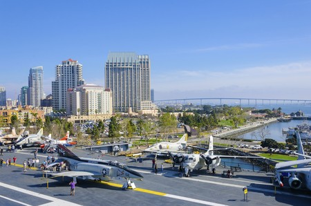 The historic aircraft carrier, USS Midway Museum moored in Broadway Pier in Downtown San Diego, Southern California, United States of America and the skyline. A battleship commissioned after the World War II.