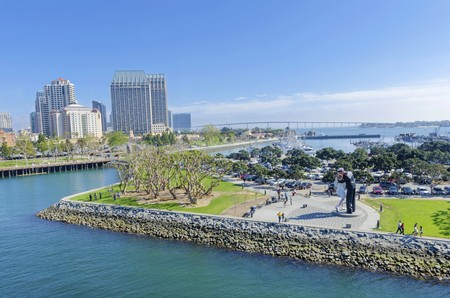 city park skyline: A view of the Unconditional surrender statue in Downtown San Diego marina in southern California in the United States of America. Some of the local architecture, commercial buildings and the coronado bridge in the city. Stock Photo