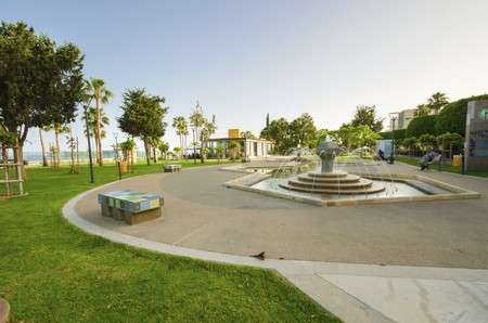 A view of Molos Promenade on the coast of Limassol city in Cyprus. A view of the walk path surrounded by palm trees, a fountain and mosaic art decorated benches, grass and the Mediterranean sea. photo
