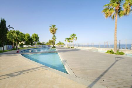 A view of Molos Promenade on the coast of Limassol city in Cyprus. A view of the walk path surrounded by palm trees, pools of water, grass and the Mediterranean sea. photo