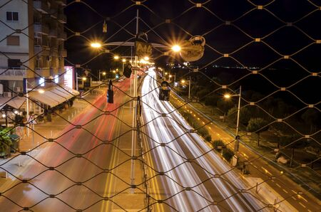 A night view of the seaside pedestrian bridge connecting the beach to GSO Sports park in Limassol, Cyprus. A view of the cable that lovers hang padlocks, the traffic on the street and the mediterranean sea. photo