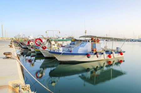 Fishing boats docked at the Limassol old port in Cyprus, next to the Marina part of the ports authority. A view of the harbor, the mediterranean sea, the water, boat and fish nets and fishing equipment.