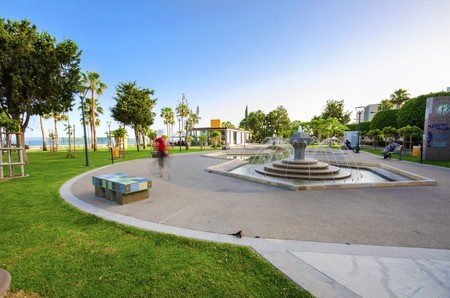 A view of Molos Promenade on the coast of Limassol city in Cyprus. A view of the walk path surrounded by palm trees, a fountain and mosaic art decorated benches, grass and the Mediterranean sea.