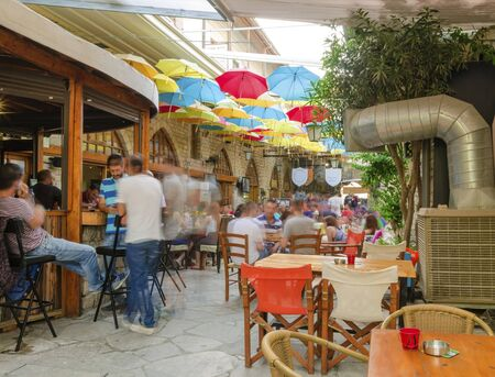 crusaders: Stoa Fylaktou in the historic medieval city center of Limassol in Cyprus. A view of the cafe, restaurant, the colorful umbrellas hang over the tables and the old decorated walls.