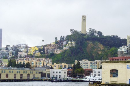coit: Coit Tower, aka the Lillian Coit Memorial Tower on Telegraph Hill neighborhood of San Francisco, California, United States of America. A view of the flutted white tower from the Fishermans wharf on the bay.