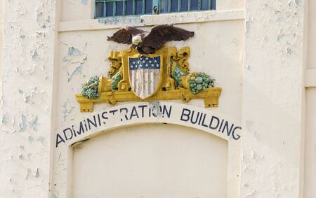 A statue of the government Seal depicting the bald eagle, coat of arms and american flag at the entrance of the Administration Building on Alcatraz island prison, now a museum in San Francisco, California, USA.