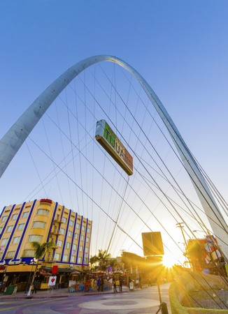 vigor: The Millennial Arch (Arco y Reloj Monumental), a metallic steel arch at the entrance of the city of Tijuana in Mexico, at zona centro a symbol of union and vigor to the new millennium and a landmark that welcomes tourists in Avenida de revolucion with a s Editorial