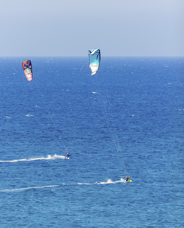 Two men kitesurfing in the crystal bays of Cyprus. A watersport whereby a kite surfer controls a power kite and rides waves on a wakeboard in the sea using the wind.  photo