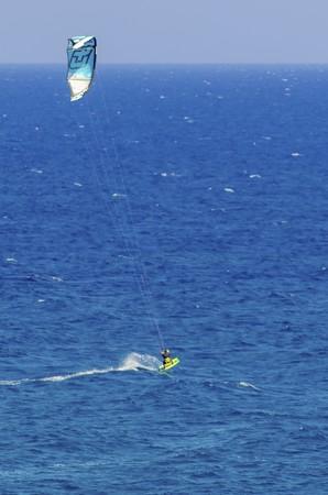 kitesurfen: Een man kitesurfen in het kristalheldere baaien van Cyprus. Een watersport waarbij een kite surfer stuurt een power kite en rijdt golven op een wakeboard in de zee met behulp van de wind. Stockfoto