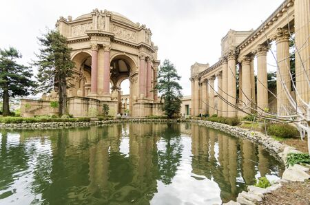 opulent: A view of the dome rotunda of the Palace of Fine Arts in San Francisco, California, United States of America. A colonnade roman greek architecture with statues and sculptures build around a lagoon.