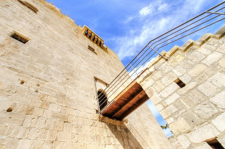 constitutes: A view of the bridge leading to the main entrance gate of the medieval castle of Kolossi. It is situated in the south of Cyprus, in Limassol. The castle dates back to the crusades and it constitutes a landmark of the area.