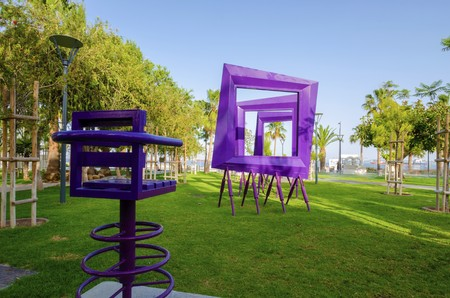 A view of Molos Promenade on the coast of Limassol city in Cyprus. A view of a modern purple art sculpture of square frames and a chair, the walk path surrounded by palm trees, grass and the Mediterranean sea.
