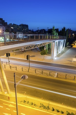A night view of the seaside bridge connecting the beach to GSO Sports park in Limassol, Cyprus. A view of the street, the wooden and glass pedestrian bridge, Fytideio sports park and paraliakos.