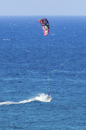 watersport: A man kitesurfing in the crystal bays of Cyprus. A watersport whereby a kite surfer controls a power kite and rides waves on a wakeboard in the sea using the wind.