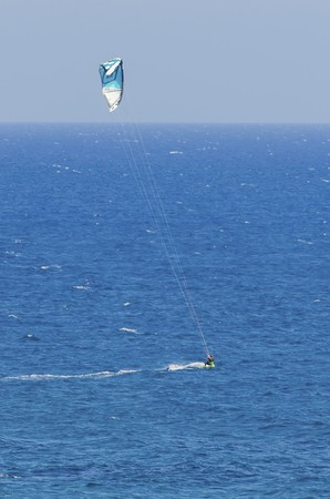 A man kitesurfing in the crystal bays of Cyprus. A watersport whereby a kite surfer controls a power kite and rides waves on a wakeboard in the sea using the wind.  photo