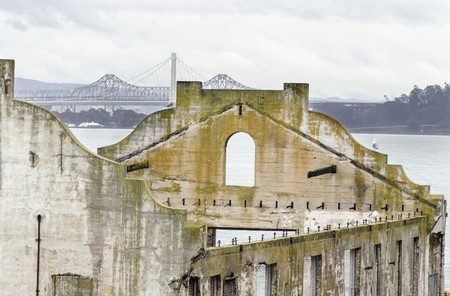 correctional officer: The Social Hall on Alcatraz island prison, now a museum in San Francisco, California, USA and Bay Bridge. A view of the stripped, burned, moldy walls and the ruins, a result of the native american occupation. Stock Photo