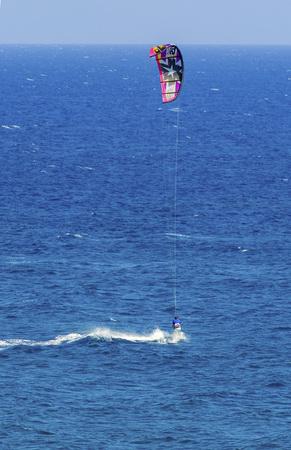 kitesurfen: Een man kitesurfen in het kristal baaien van Cyprus. Een watersport waarbij een kite surfer stuurt een power kite en rijdt golven op een wakeboard in de zee met de wind.