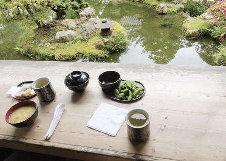 japanese tea garden: The Japanese Tea  Garden in Golden Gate Park in San Francisco, California, United States of America. A view of green tea, miso soup, sweets and edamame from the tea house next to a pond that create a relaxing scenery. Stock Photo