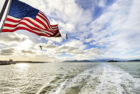 View of San Francisco Bay, the Golden Gate bridge, seagulls flying, the american flag waving and Alcatraz island at sunset from a ferry in California, United States. Stock Photo
