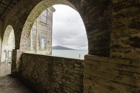 incarceration: The Alcatraz Penitentiary island, now a museum, in San Francisco, California, USA. A view of the brick stone arched building and windows overlooking the Frisco Bay and Oakland from the historic federal prison.