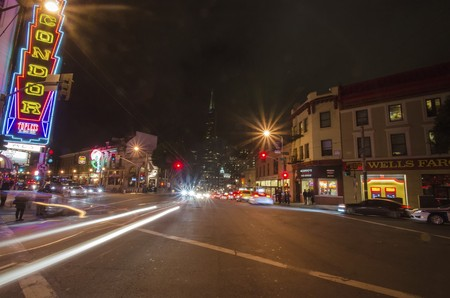 A night view of Little Italy at the intersection of Columbus and Broadway in North Beach, San Francisco, California, United States of America. restaurants, city and car light trails.