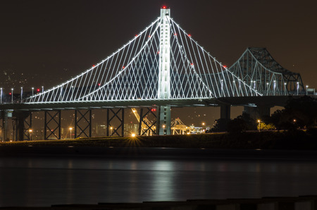 san fran: A night view of Bay Bridge in San Francisco, California, United States of America. A bridge suspended by cables over the Frisco Bay connecting San Fran to Oakland and through Treasure Island. Stock Photo