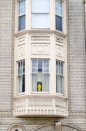 Exterior detail of victorian architecture house in San Francisco, California, United States of America. A view of the window balcony and brick wall Stock Photo