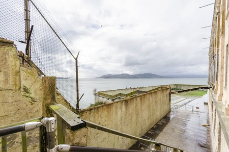 The Recreation Yard on Alcatraz Penitentiary island, now a museum, in San Francisco, California, USA. A view of the exercise yard, the prison fence, the cellhouse, the Treasure island and Bay Bridge.
