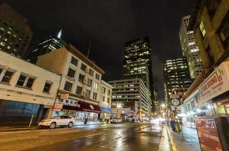 Night view of San Francisco Chinatown in northern California, United States of America. A view of the cityscape, city skyscrapers, illuminated streets and Chinese signs over the shops.