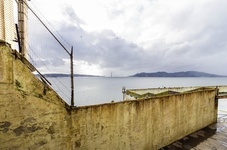 interstate 80: The Recreation Yard on Alcatraz Penitentiary island, now a museum, in San Francisco, California, USA. A view of the exercise yard, the prison fence, the cellhouse, the Treasure island and Bay Bridge.